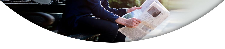 فردی نشسته در حال خواندن روزنامه- آژانس تبلیغات کربن