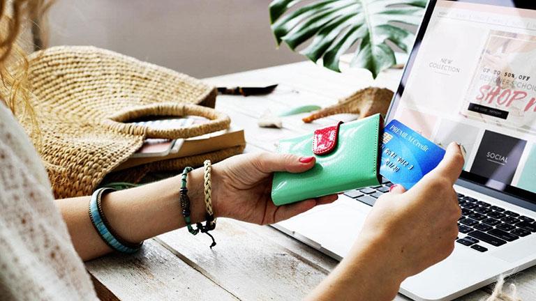 دست یک خانم در حال دراوردن کارت بانکی در کنار کیف و لپ تاپ- آژانس تبلیغاتی - آژانس کربن- تبلیغات